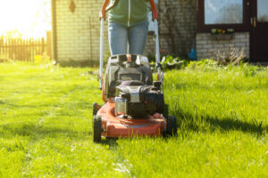 A woman mowing an overgrown lawn.