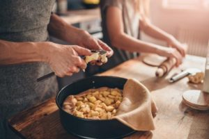 Two people preparing the ingredients for an apple pie.