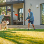 family and dog playing in a lawn