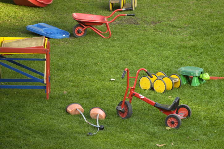 A tricycle, child's wheelbarrow, and other toys cluttering a backyard.